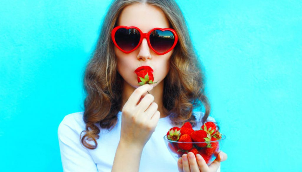 Portrait pretty woman with many strawberry over colorful blue